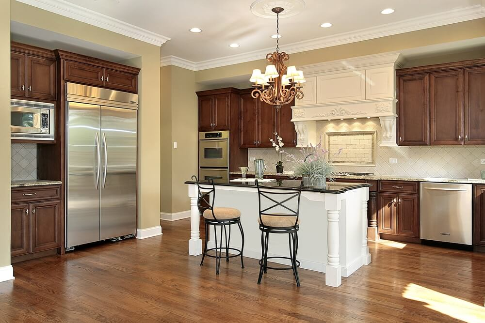 Brightly lit kitchen is highlighted by a white island with black countertop, seated between dark wood cupboards and hardwood flooring.