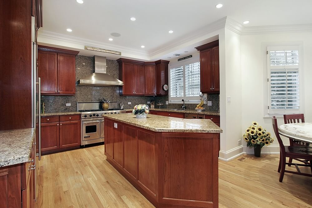 This kitchen features matching countertops and backsplash as well, set against cherry wood cabinets and island, with light hardwood flooring and white walls.