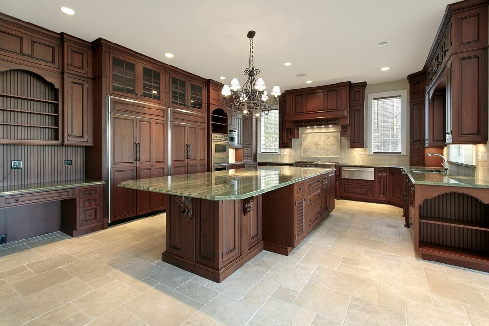 Dark rich wood tones really stand out in this light kitchen featuring tile flooring and green granite countertops.