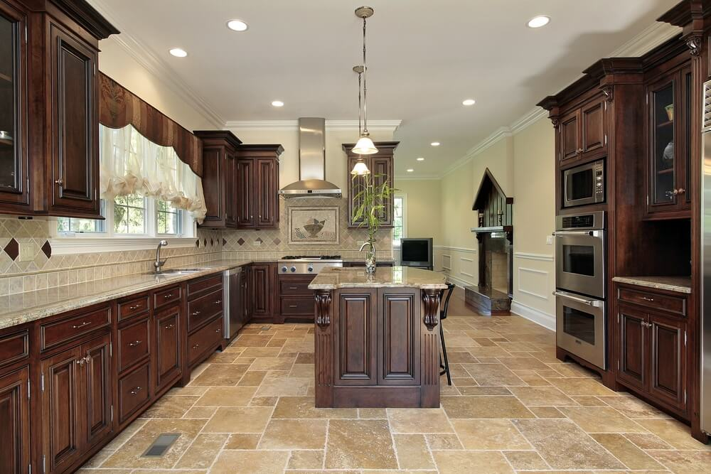Stately cabinet design in this kitchen is strengthened by dark wood over the light tile flooring and backsplash.
