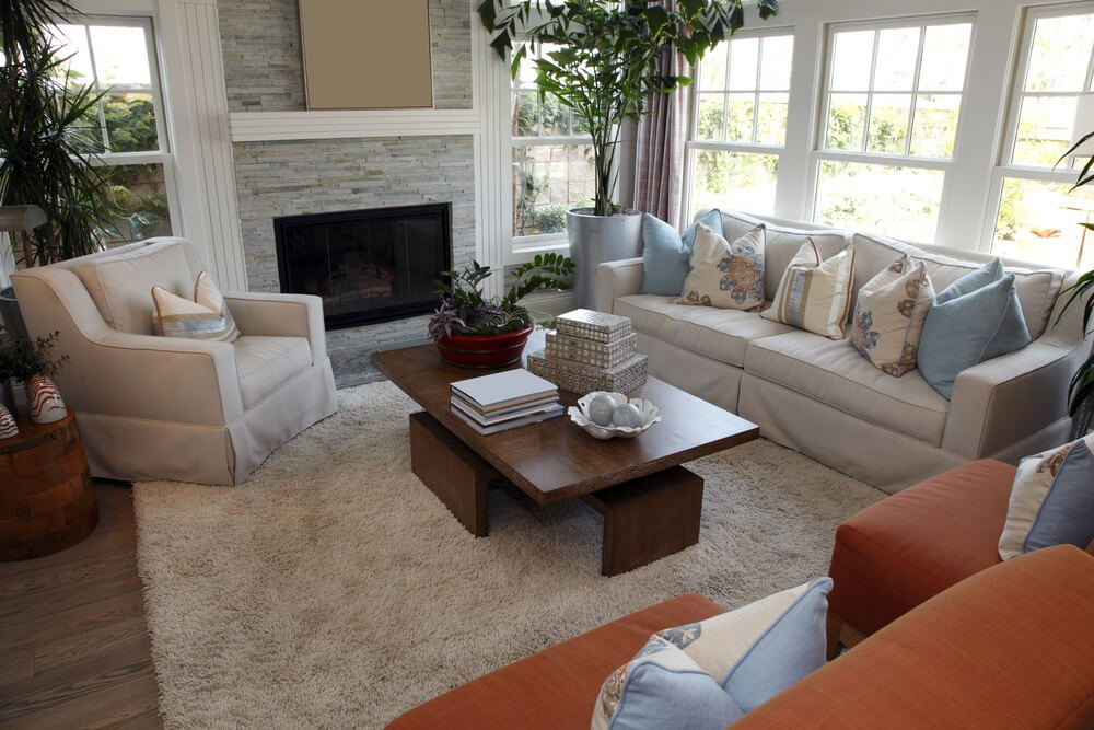 Living room space with two reddish brown chairs, one beige sofa and one beige armchair all around a rectangle modern wood coffee table. Fireplace is framed with stone wall and white crown molding.
