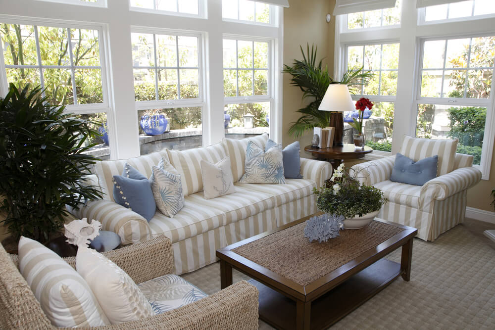 Cottage style solarium living room with beige and white striped furniture, one armchair being a wicker frame. Living room enjoys plenty of natural light from wrap-around windows.