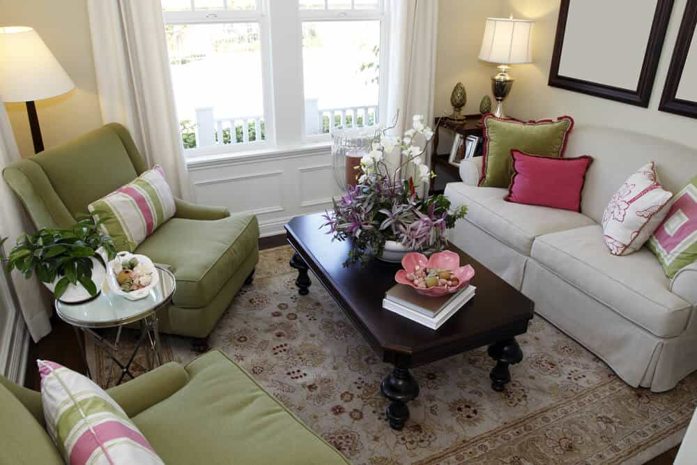 Tiny living room space in colorful design with green armchairs and off-white sofa. Pillows throughout the room are green, off-white and pink adding splashes of color to the space.