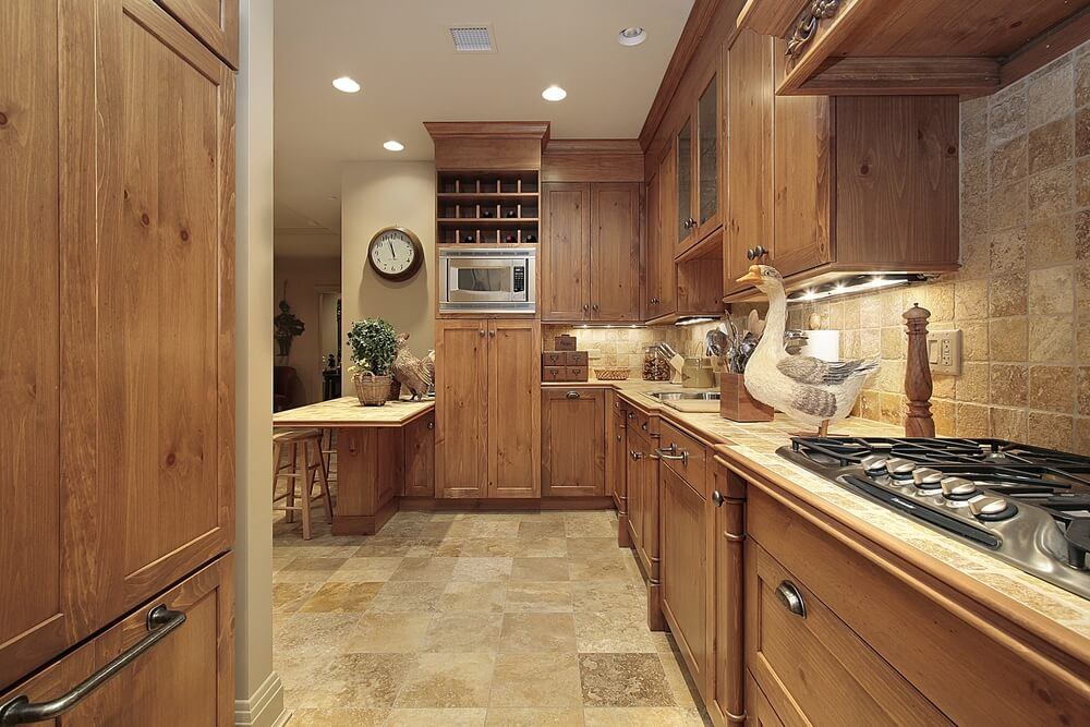This kitchen is all about uniform coloring, with the wood cabinet doors on the darker end, and sand colored tile flooring and backsplash at the lighter end.