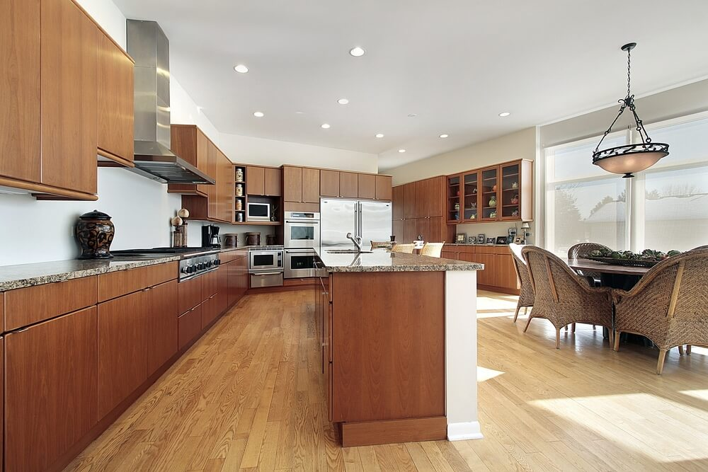 Uniformly minimal kitchen features smooth dark wood cabinets and shelving in an expanse of natural hardwood flooring.