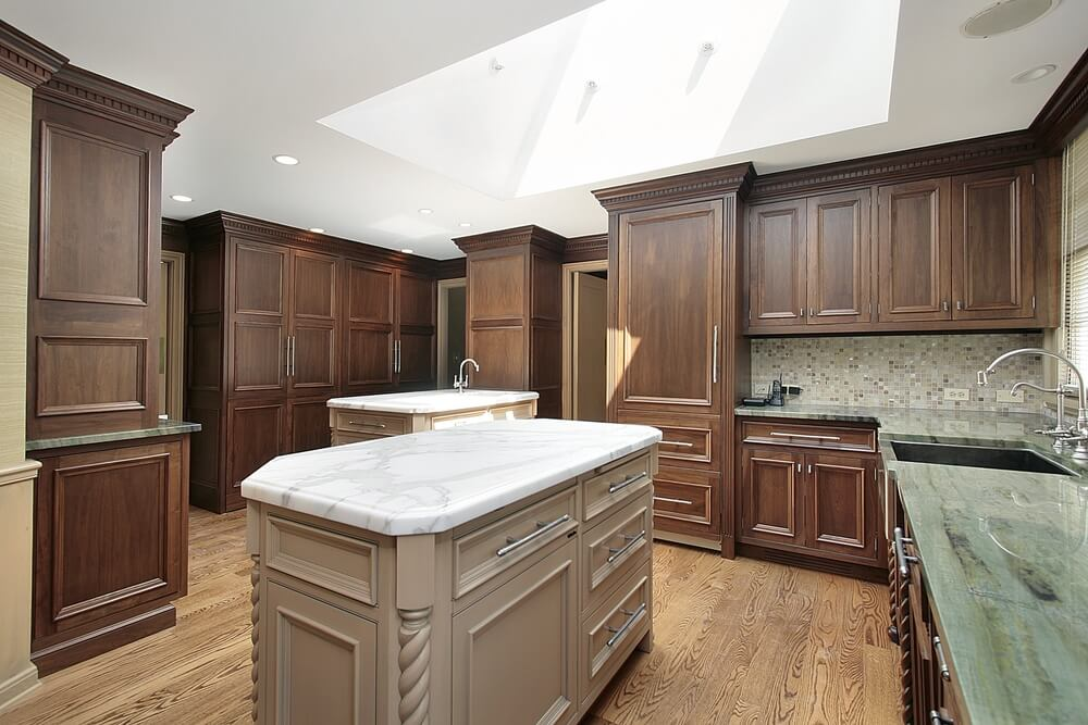 Unique color combination in this kitchen features subtle dark colored wood cabinets floor to ceiling, dual light islands, and large skylight.