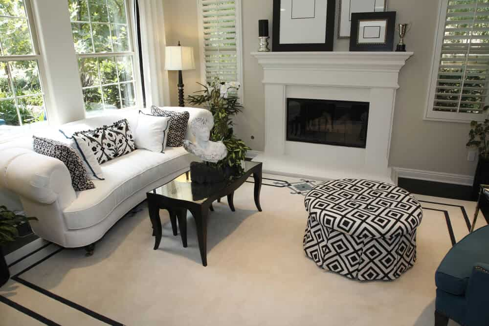 Small living room mainly in white with a black and white patterned round ottoman and sofa pillows. Off-white and black bordered rug forms the flooring of the entire space.