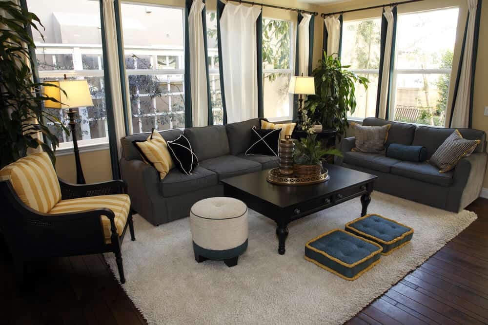 Living room situated in the corner of a condominium with wrap-around windows letting in plenty of light. Rome is a grey, blue and brown color scheme with two sofas and one armchair placed on an off-white area rug on top of dark brown wood floors.