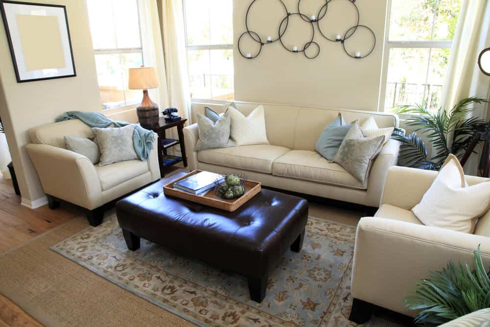 Bright living room with two matching white armchairs and one white sofa. Brown leather ottoman also serves as a coffee table.