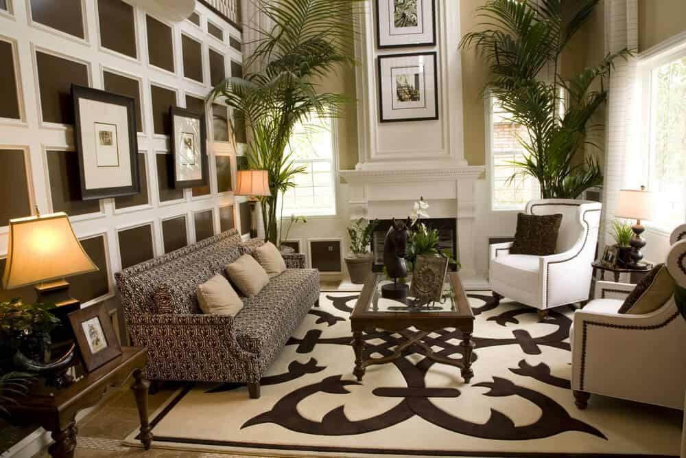 Living room with elevated ceiling. Two white armchairs with one long sofa placed on large patterned area rug. The highlight of the room is the white painted wood frames on dark brown wall.