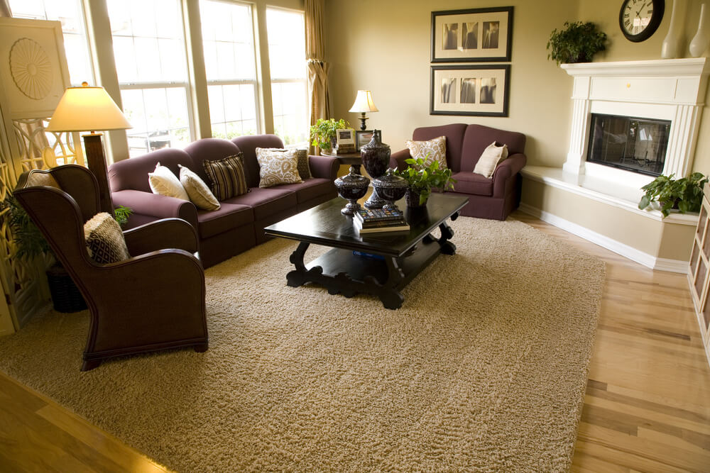 Living room with the fireplace in the corner built in a diagonal formation facing the entire living room made up of matching purple living room furniture.