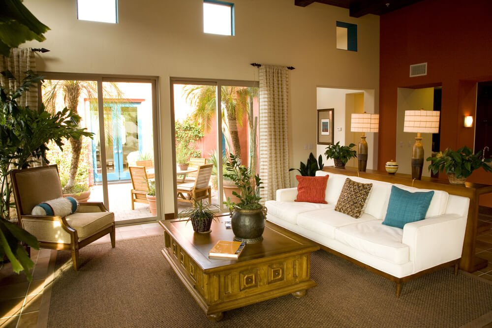 Two-story living room looking out on a courtyard. While it's sparse in decoration, the white sofa with color pillows demonstrates how a white sofa with bright pillows can create a great living room design.