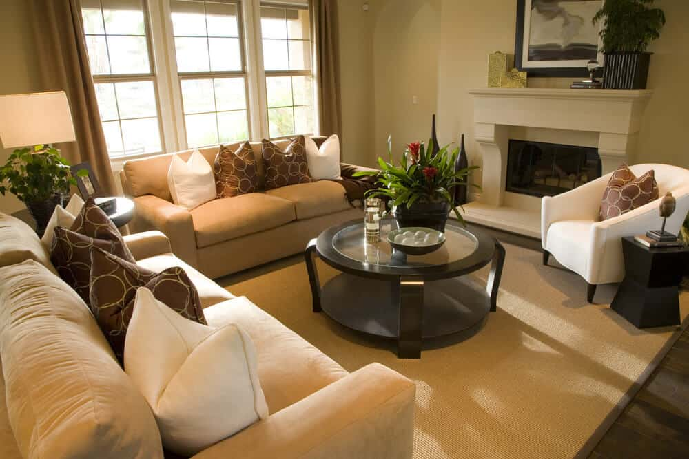 Square living room with a round wood and glass coffee table. Two sofas and one white armchair make up the rest of the furniture along with a small round coffee table in between the two sofas.