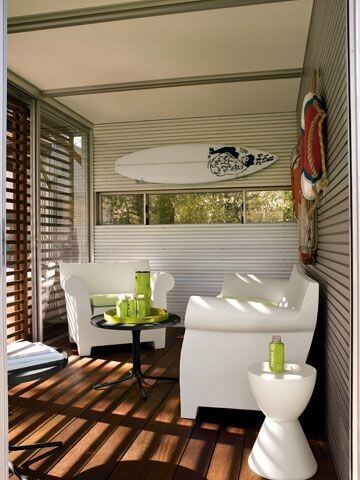KitHaus interior flush with bright white furniture, black table and details like surfboard and life rings mounted on walls.
