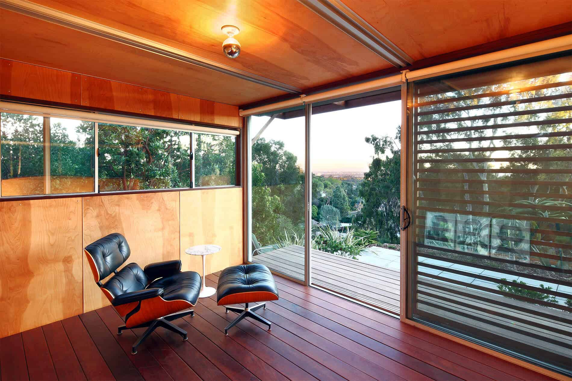 Interior decked out in rich red wood flooring with lighter natural wood walls and ceiling, full glass view of outdoors with shade slats.