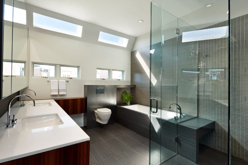 Primary bathroom features all-glass shower, white countertops, red wood cabinetry, and dark wood floor extending to bath surround.