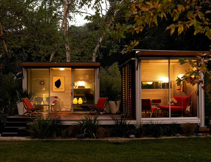 This KitHaus features two modules set on a shared patio space. Red furniture and white interiors cast bright contrast.