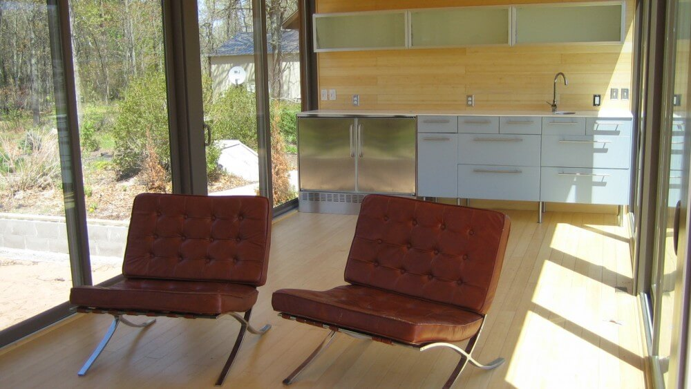 Opposite view reveals kitchen area with white and metal cabinetry, glass door shelves mounted on wall, and twin leather living room chairs in foreground.