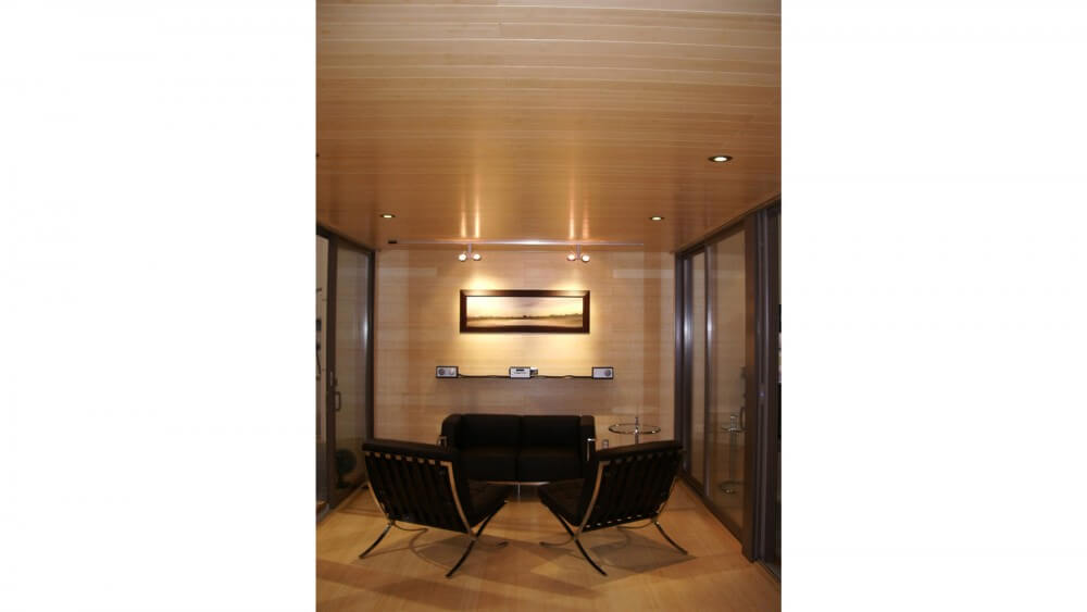 Interior features extensive natural wood tones on all surfaces, from floor to ceiling. Black and metal furniture with glass tables make up living room space.