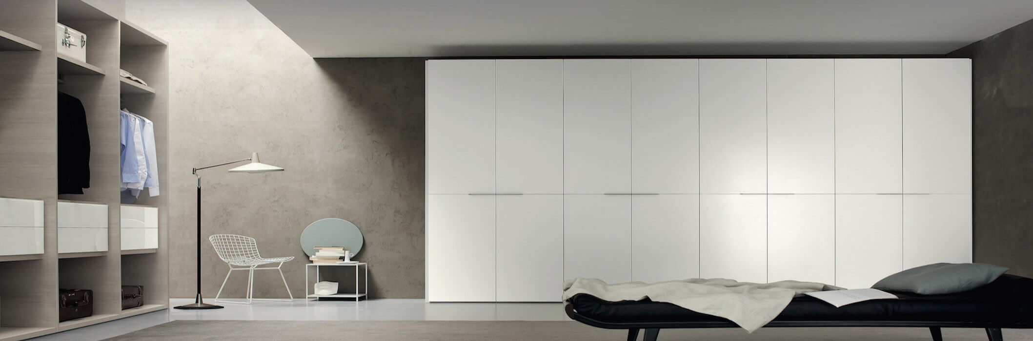 Ample space in this bedroom provides room for expanse of white flush wall storage panels, with open closet shelving across from flat black bed on slate grey floor with darker toned walls.