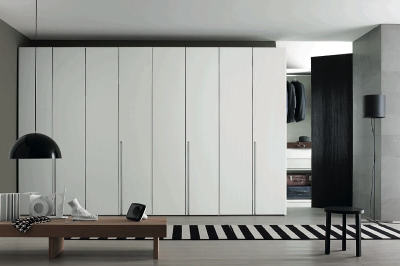 Here we have another example of the floor to ceiling uniform, flush door panels creating a detailed wall surface. White contrasts with large black panel, black and white room-length rug, and lone black stool. Natural wood toned bench seats art pieces with half-sphere hung lighting above.