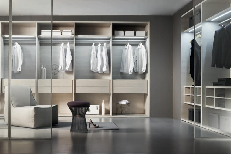 This intricately detailed walk in closet space is divided by floor to ceiling glass panels, and features interlocking, inner-lit shelving space with built in drawers. Central area features purple stool and grey chair over singular rug on flat grey floor.