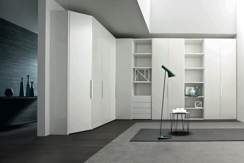 This super minimalist design features the contrast of white vertical spaces with black and grey flooring. Full height cabinet doors appear flush on wall with built-in shelving interspersed.