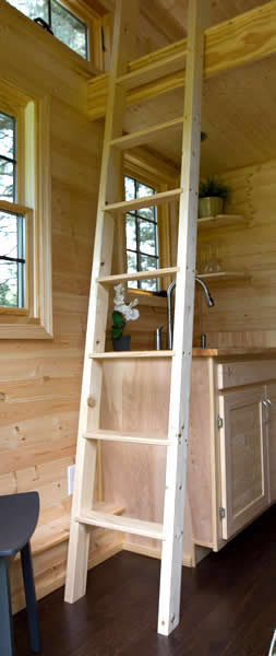 Interior is replete with natural unpolished wood, with ladder over kitchenette leading to loft.