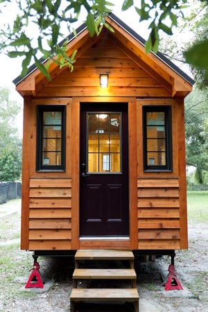 This is an identical tiny home, situated in a more traditional yard setting. Black door and window surrounds add contrast to the exterior.