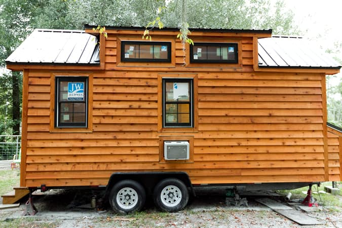 Side view of home, showcasing lower and upper windows, built-in air conditioning unit, and wheels for transport.