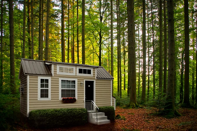 This Tiny Home is painted beige with siding and white window surrounds. Full porch sits at front.