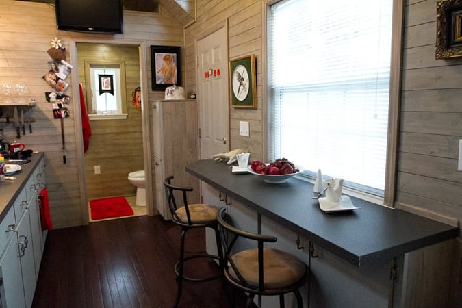 Bar style dining area sits across kitchenette. Bathroom in rear.