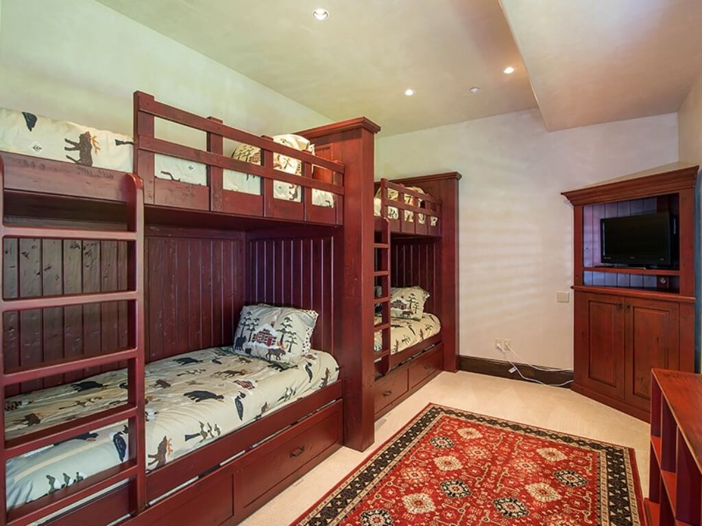 Children's bedroom features lush red wood throughout, including twin bunk beds, corner entertainment stand, and bookshelves. Red patterned rug ties the room together.
