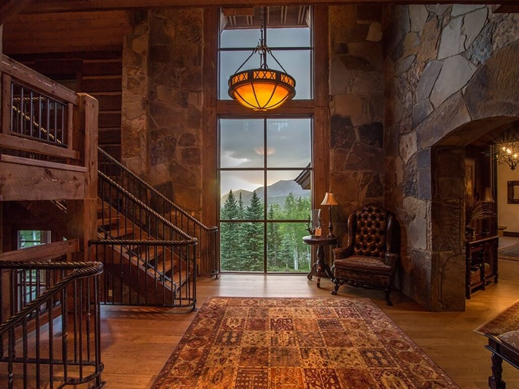 Head on view of main landing, with stone wall arch on right, floor to ceiling windows framed in exposed wood beams, staircase on left, and central patterned rug over hardwood flooring.