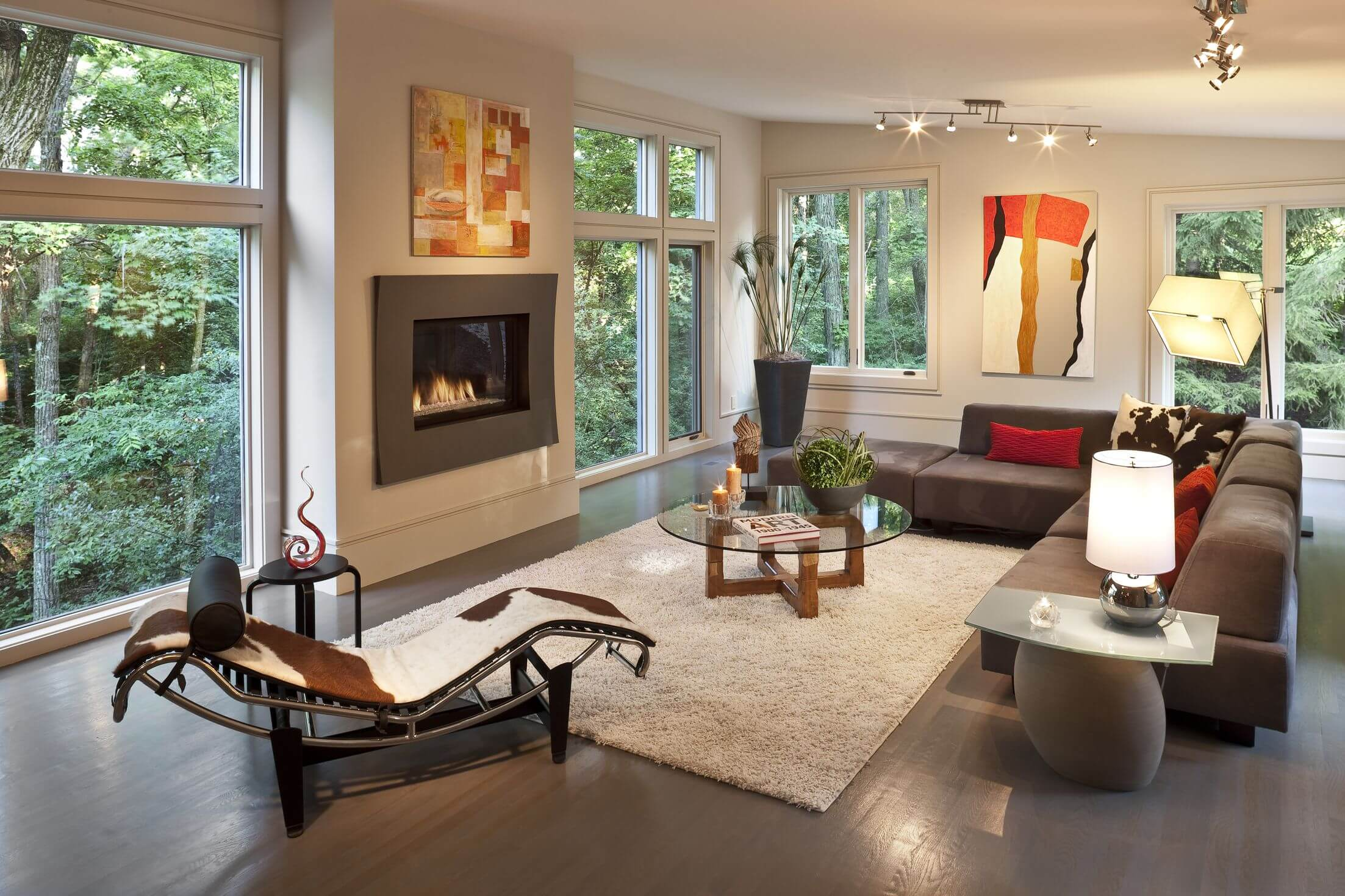 Sloped white ceiling over dark wood flooring in this living room holding modern armless brown sofa with red and cow-pattern pillows. White shag rug at center olds wood and glass coffee table, while cowhide chaise lounge sits on left.