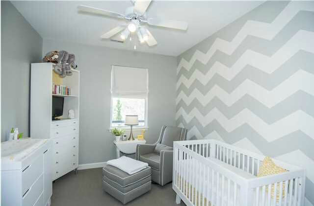 Small nursery room with an interesting wall design lighted by ceiling fan light.
