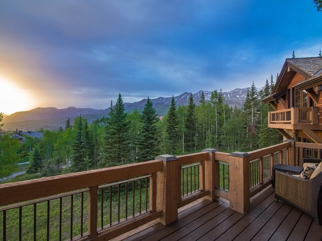 Expansive view of mountains from the upper balcony, with natural wood and metal railings wrapping dark stained wood deck.