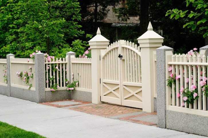 This white fence with spiked tops is framed in marble lower structure and dividing posts.
