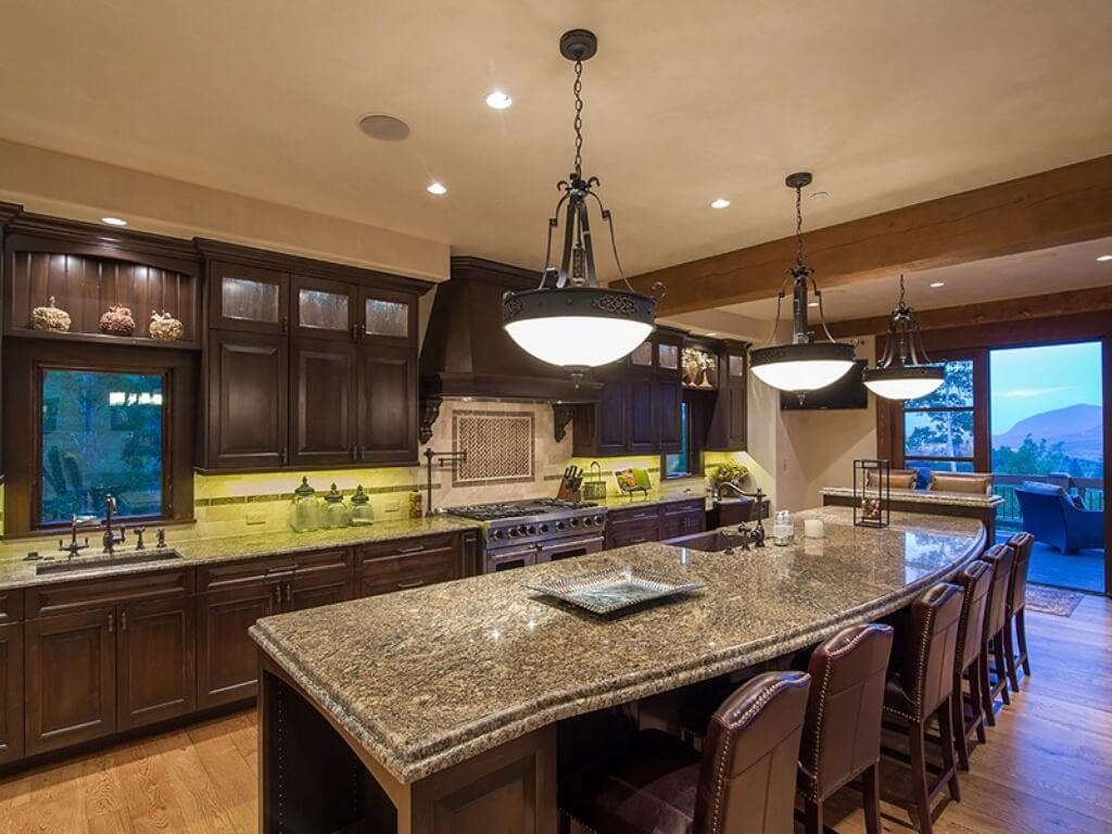 This large kitchen has dark wooden cabinetry along the walls on the opposite side of the dark wooden kitchen island paired with dark brown leather upholstered stools and topped with dome pendant lights.