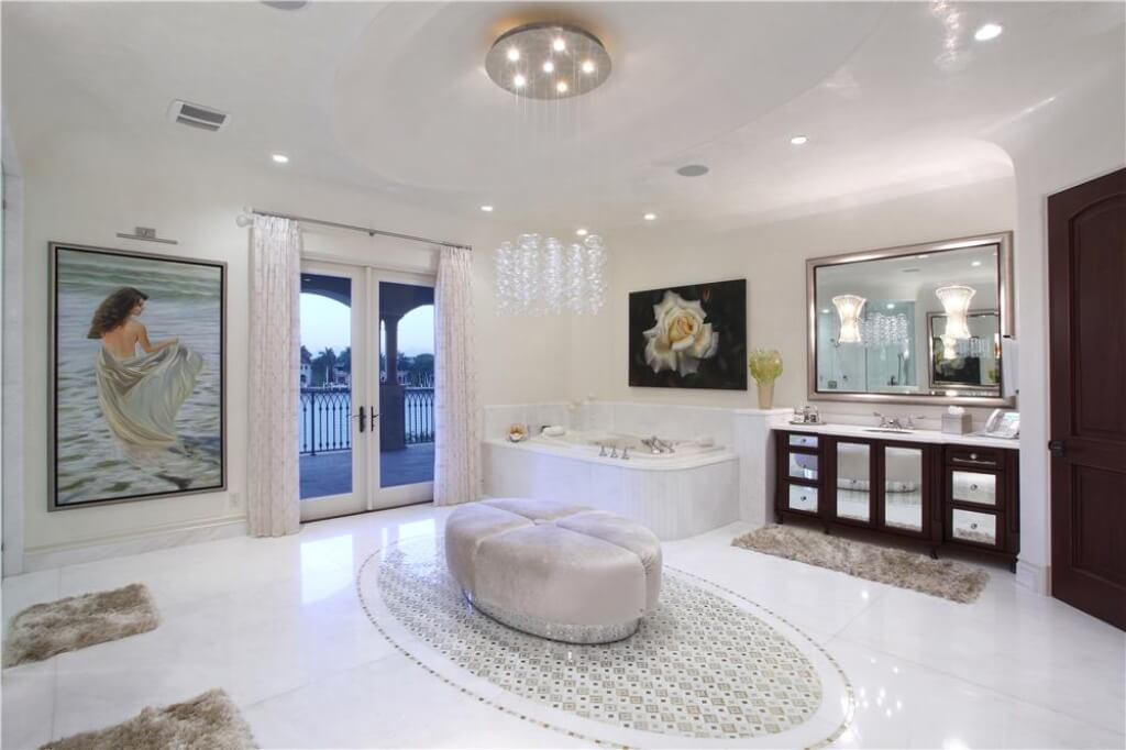The luxurious bathroom is complete with marble floors, an intricate mosaic, and a beautiful corner tub perfect for relaxation.