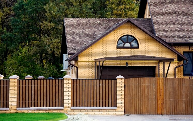 This privacy fence features natural wood sandwiched between layers of brick matching the yellow hued home.