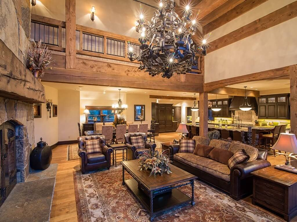 This view 0f the living room highlights the massive stone fireplace with natural wood mantle on left, leather and cloth furniture gathered around natural wood and wrought iron coffee table, and overlooking catwalk behind large metal chandelier.