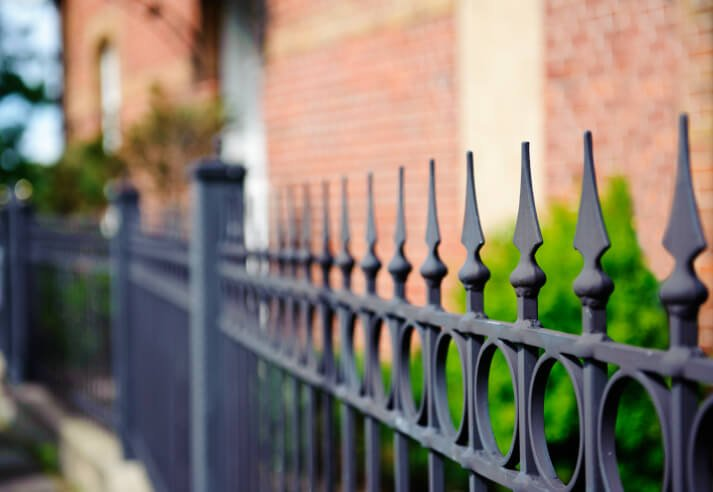 This wrought iron fence features spike caps and circular design flourish.