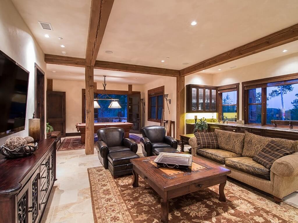 Lower level family room featuring twin leather armchairs with ottomans and brown cloth sofa around large carved wood coffee table, with floral patterned rug over light marble flooring, and exposed beams framing the entire space.