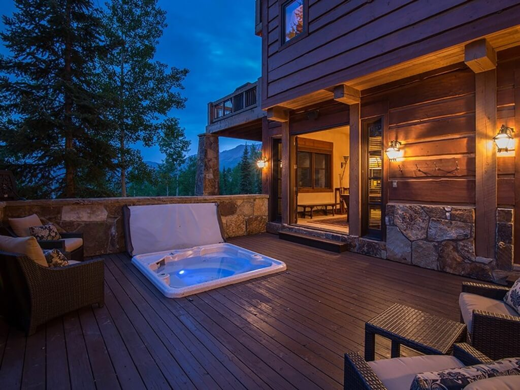 Elevated wood patio features built-in jacuzzi, with dark wicker furniture surrounding. Stone lower wall, natural wood siding, and exposed beams all flow through exterior of home.