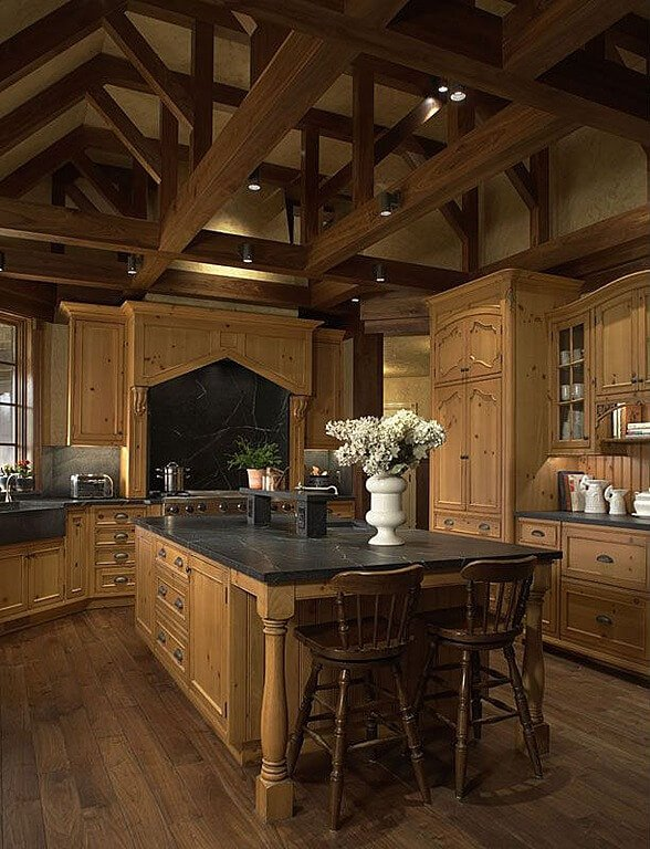Singular tone of natural wood cabinetry unifies this kitchen, sandwiched between dark exposed ceiling beams and matching hardwood flooring. Black marble topped island commands the center.