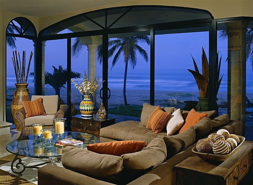 Tropical themed living room is filled with grey pillow backed sectional, glass topped coffee table, wicker armchair and chest-style side tables, with full ocean view courtesy of floor to ceiling windows.