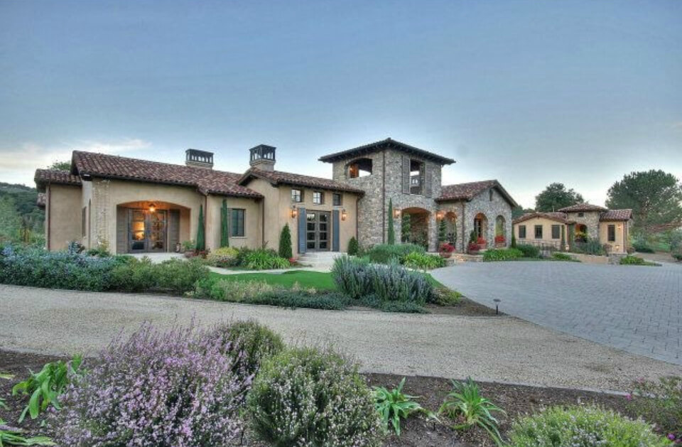Panoramic view of the home from the front. The middle stone tower features a covered patio with great views.