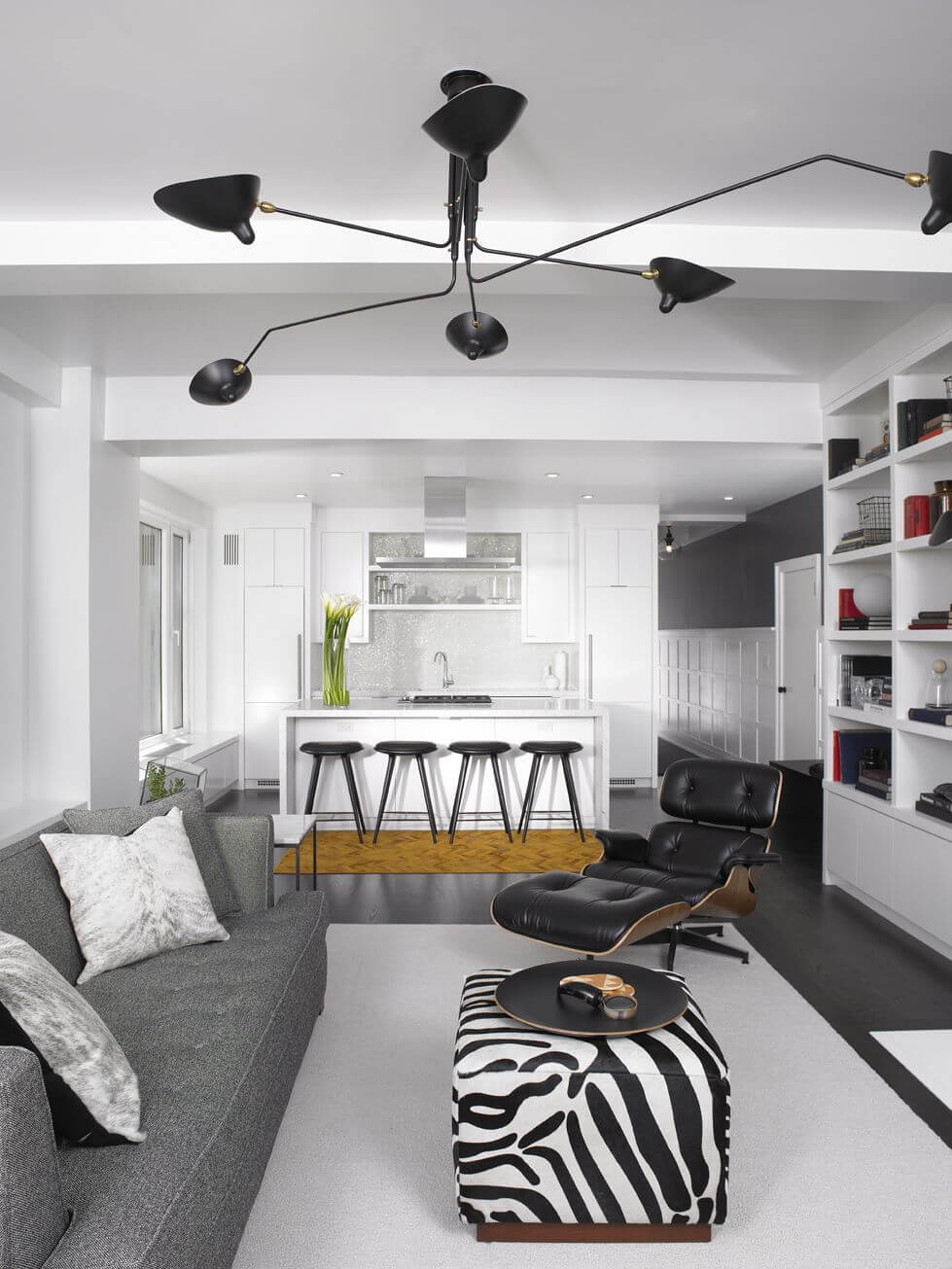 This small apartment living room in an open concept living space features a small zebra print ottoman functioning as a coffee table in between a grey sofa and black reclining chair