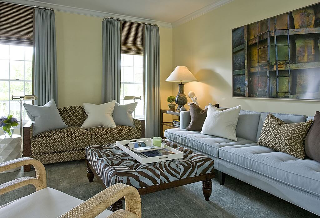 This small living room includes a brown and white zebra print ottoman with wood frame
